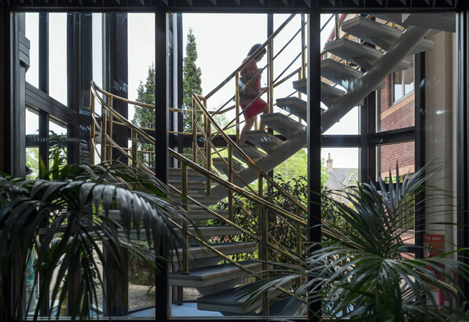 Spiral staircase, tropical plants, woman walking up stairs.