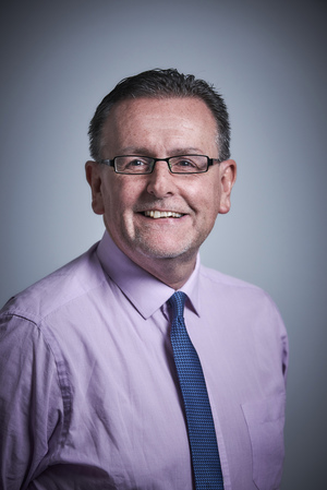 Man wearing glasses, purple shirt and dark blue tie.