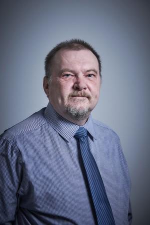 Man wearing blue shirt and dark blue tie.